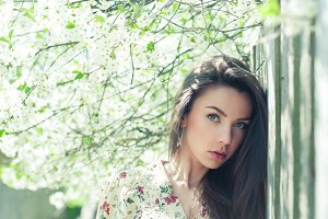 Pretty girl near blossoming tree
