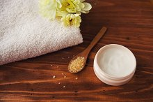 sea salt  beauty cream with flower and  towels    on  wooden background