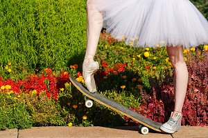 Legs of ballerina on skateboard.