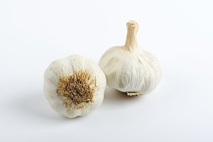 Heads of garlic on white background