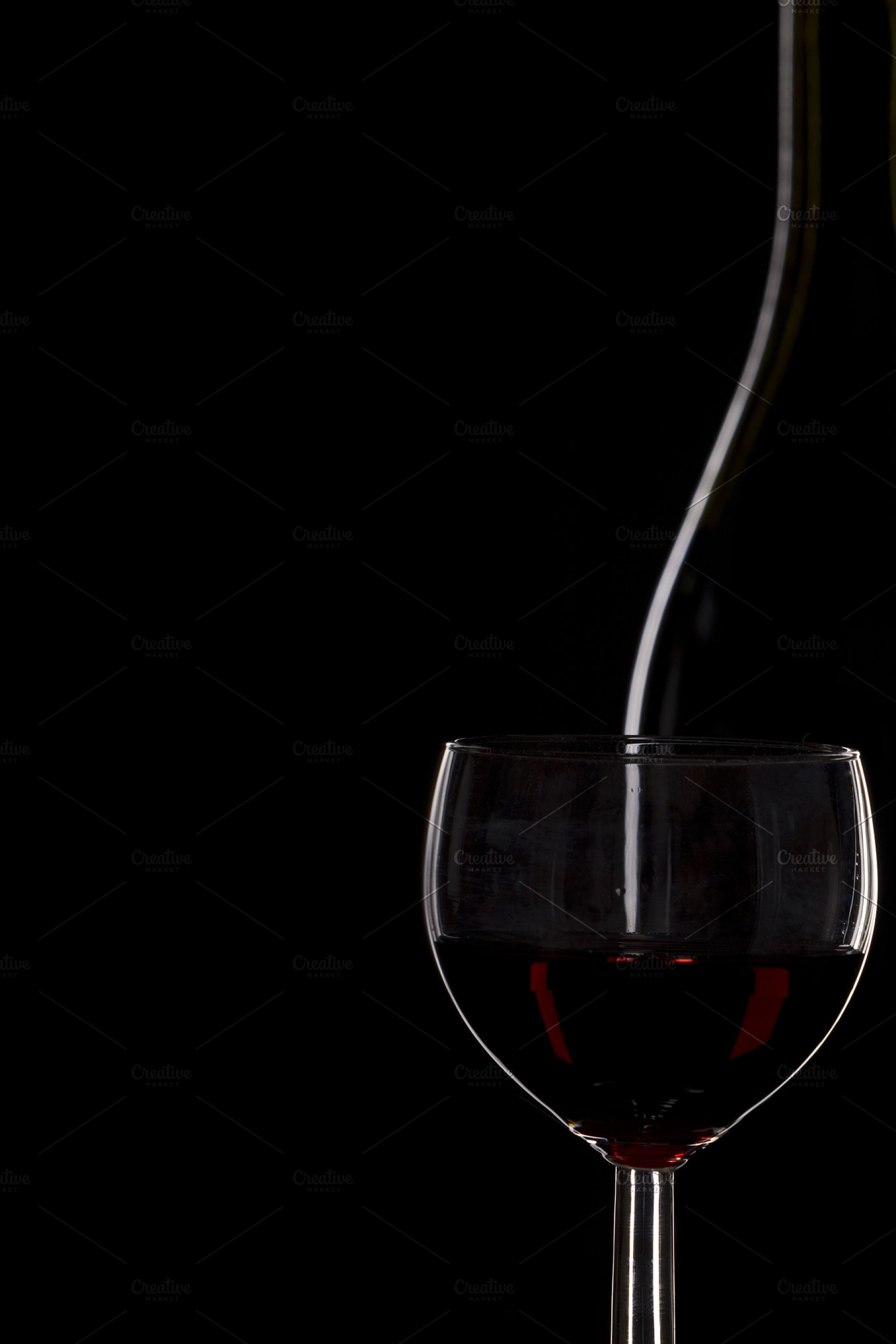 5d1ad3bd05e4 Bottle of wine and a glass of wine on a black background