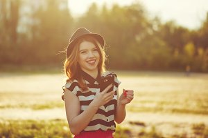 Lovely girl in hat holding phone