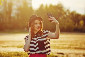 Lovely girl in hat makes Selfie
