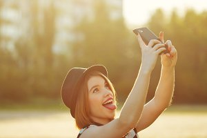 Cute girl in hat make street selfie
