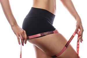 Girl measuring tape thigh.