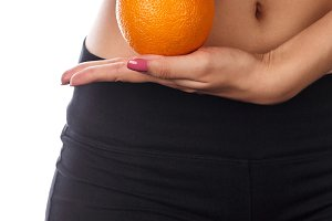 Slender woman holds an orange.