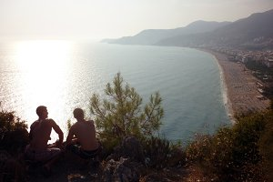 Two man sitting on rocky cliff