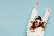 portrait of cheerful fashion hipster girl going crazy making funny face and dancing. Blue color background.