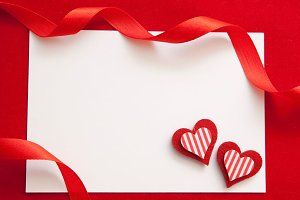 Two hearts, red ribbon and card