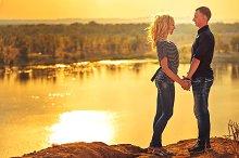Loving couple holding hands. Sunset