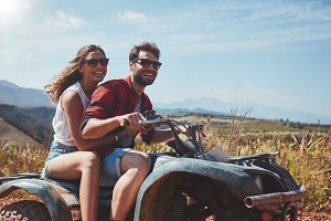 Young couple driving a quad bike