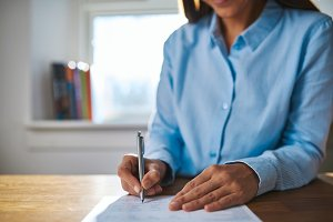 Businesswoman writing on a document
