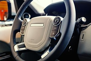 Luxury SUV Interior: Multifunctional steering wheel with control buttons and dashboard, shallow depth of field