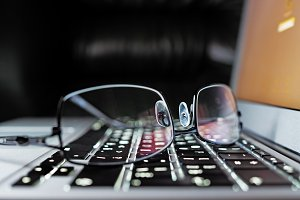 Reading eyeglasses on an elegance laptop keyboard, shallow depth of field
