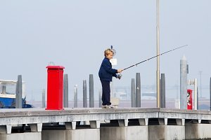 Venice, Italy - October 06, 2012: Little boy with a fishing rod catches a fish