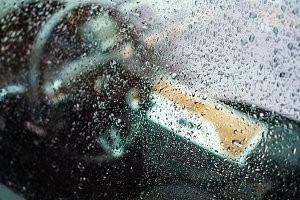 Raindrops on luxury car window, shallow depth of field