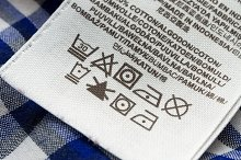Clothing labels with laundry care symbols close-up. Shallow depth of field.
