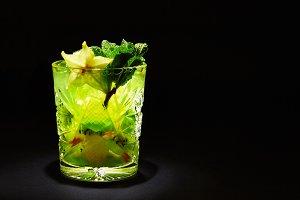 Green cocktail mojito on dark