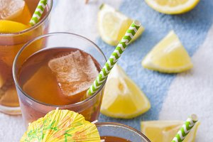 Ice tea with lemon on a beach towel