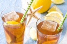Ice tea with lemon on summer towel