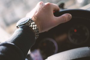 Close-up of man's hand on steering wheel. Vintage look. Shallow depth of field.
