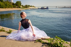 Ballerina sitting on river bank.