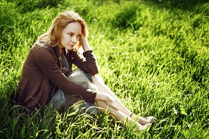 Young woman is sitting on the grass