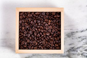Fresh coffee beans in box on marble