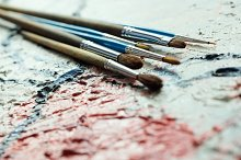 Paintbrushes on oil painting canvas. Shallow depth of field.