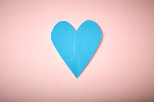 Blue paper heart on pink paper
