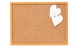 Heart shaped paper notes with envelope pinned into brown corkboard