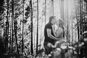 Black white photography romantic young couple kissing on background summer forest