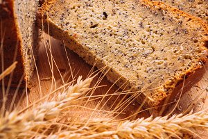 Close slice of fresh bread with poppy seeds and wheat ears on wooden background