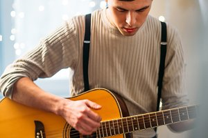 Young man sitting at home and playing guitar dramatic