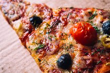 pieces of pizza with olives, cheese and salami sausage