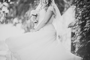 Black white  photography stylish beautiful happy bride holding  bouquet  flowers on a background of trees in the summer park full length