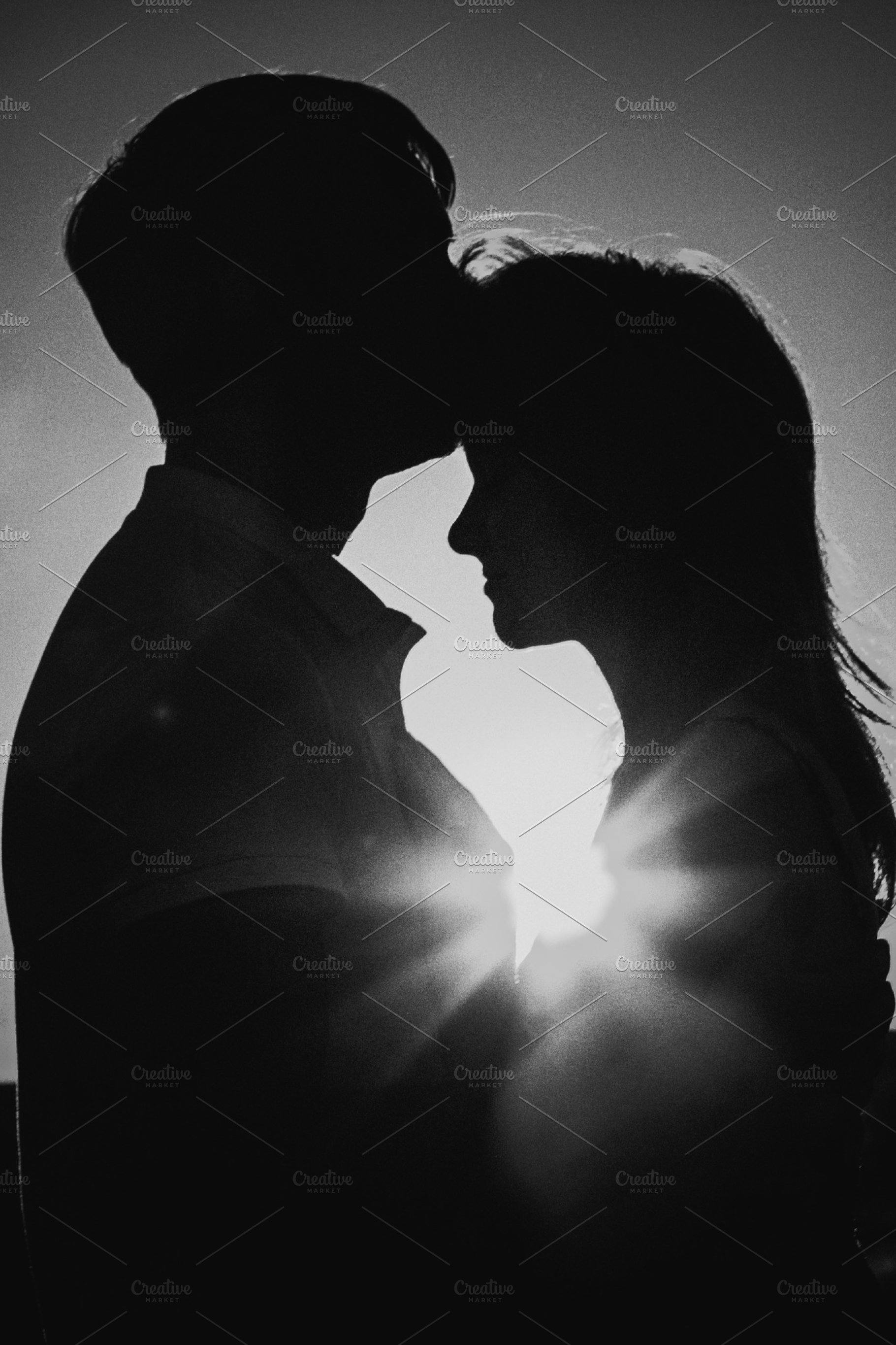 Black white photography romantic silhouette couple standing and kissing on background su