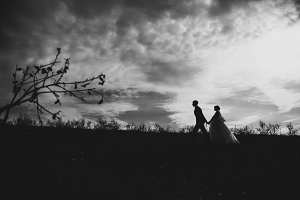 silhouettes of young bride and groom on the background sky