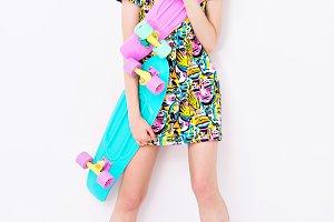 fashion sexy vogue model in colorful dress with bright ornament promote longboards in studio.