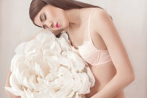 Pretty girl in pink underwear with large paper flower