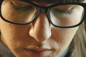 Beautiful woman in big black glasses reading