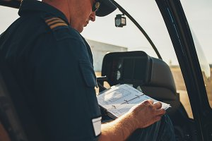 helicopter pilot reading a manual