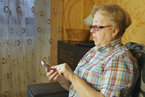 Old woman using smartphone at home