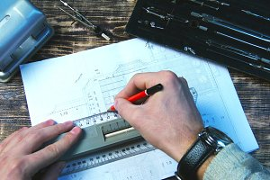Drawing a pencil line on the ruler on the drawing sheet