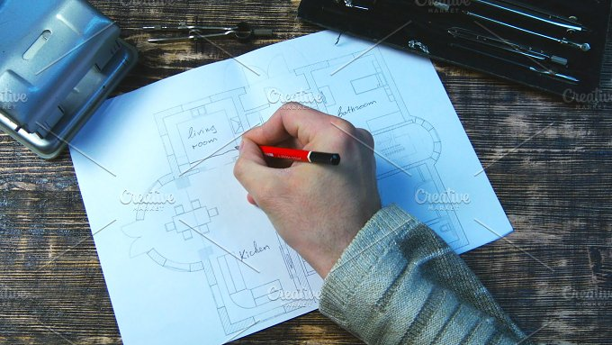 Man draws a draft. Indicates dimensions of rooms - Architecture