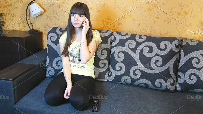 Young woman ltalking on the phone. Boyfriend brought her chips - Technology