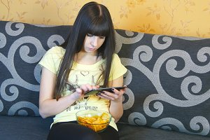 Young woman using electronic tablet sitting in sofa end eating chips