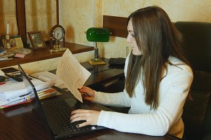Businesswoman typing document on laptop at office