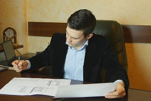 Young businessman working with documents at desk in office