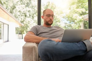 Mature man on a sofa using laptop